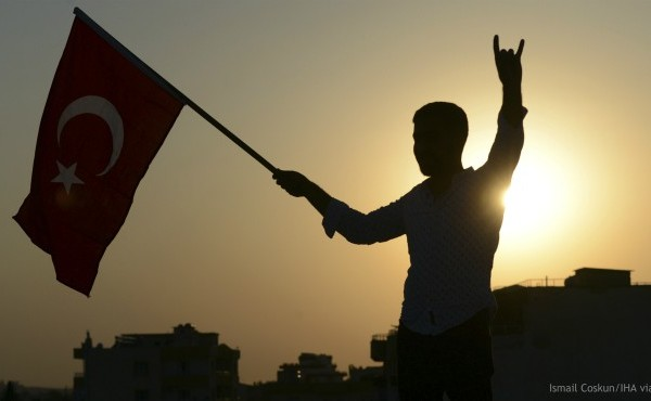A Turkish youth celebrates with a national flag after news about Syrian town of Tal Abyad, in Turkish border town of Akcakale, in Sanliurfa province, Sunday, Oct. 13, 2019. (Ismail Coskun/IHA via AP)