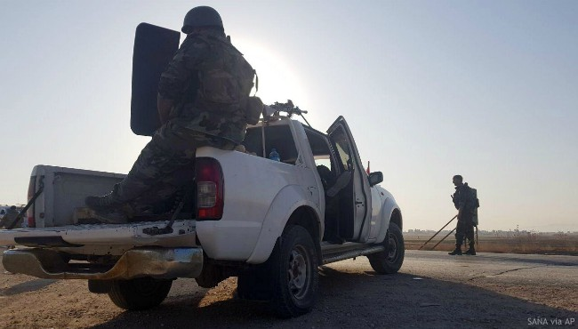 In this photo released by the Syrian official news agency SANA, Syrian troops deploy in the northern town of Tal Tamr, Monday, Oct 14, 2019. (SANA via AP)