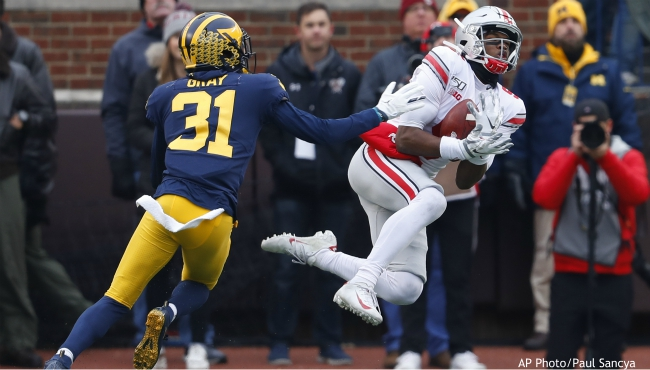 Ohio State wide receiver Garrett Wilson (5) catches a 47-yard pass as Michigan defensive back Vincent Gray (31) defends in the first half of an NCAA college football game in Ann Arbor, Mich., Saturday, Nov. 30, 2019. (AP Photo/Paul Sancya)