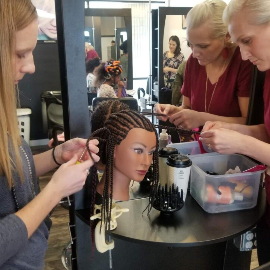 A photo of participants of Mosley School of Cosmetology's Hair Hope program in Kentwood learning how to style black hair.
