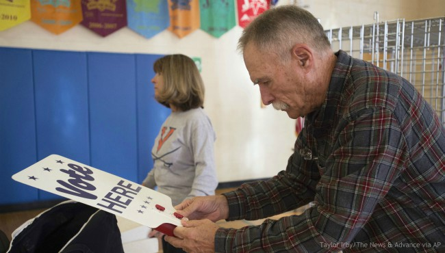 """Harry Ford, right, puts together a """"vote here"""" sign at a polling station set up at Boonsboro Elementary School in Bedford, Va., Monday, Nov. 4, 2019. (Taylor Irby/The News & Advance via AP)"""