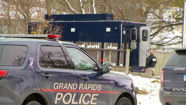 A photo of officers looking for a suspect wanted for a weapons charge in a Grand Rapids home.