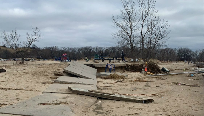A photo of a sidewalk ripped up by water from Lake Michigan at Holland State Park on Nov. 28, 2019.