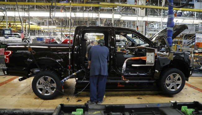 In this Sept. 27, 2018, file photo a United Auto Workers assemblyman installs seating in a 2018 Ford F-150 truck being assembled at the Ford Rouge assembly plant in Dearborn, Mich. (AP Photo/Carlos Osorio, File)