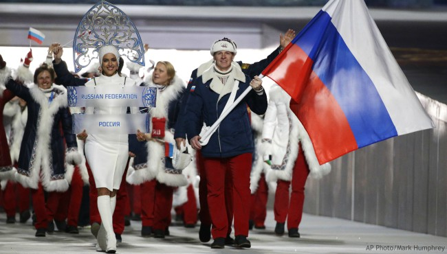 In this Feb. 7, 2014 file photo Alexander Zubkov of Russia carries the national flag as he leads the team during the opening ceremony of the 2014 Winter Olympics in Sochi, Russia. at left is model Irina Shayk carrying the Russian placard. (AP Photo/Mark Humphrey, file)