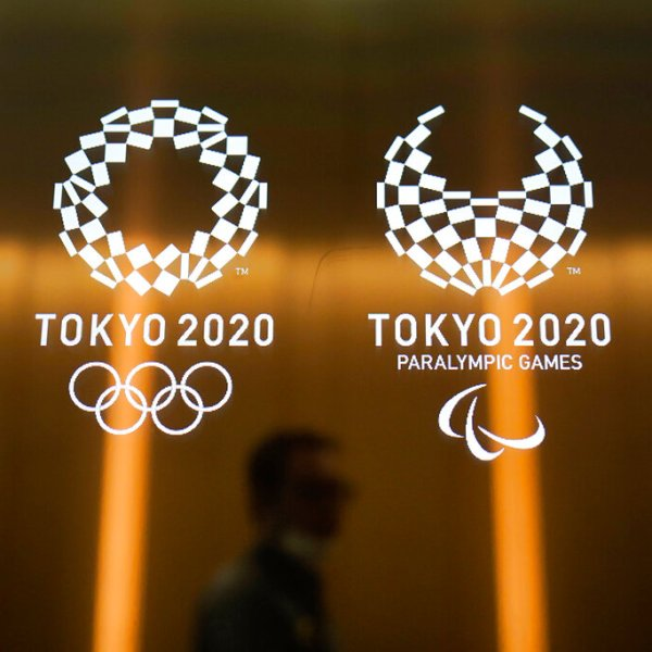 In this June 11, 2019, file photo, a man walks past the Tokyo 2020 Olympic logos in Tokyo.(AP Photo/Jae C. Hong, File)