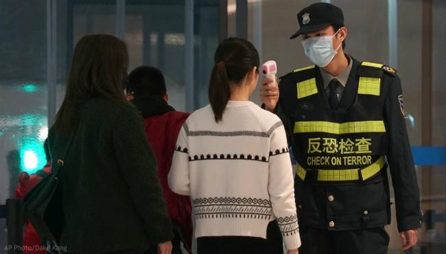 An airport staff member uses a temperature gun to check people leaving Wuhan Tianhe International Airport in Wuhan, China, Tuesday, Jan. 21, 2020. (AP Photo/Dake Kang)