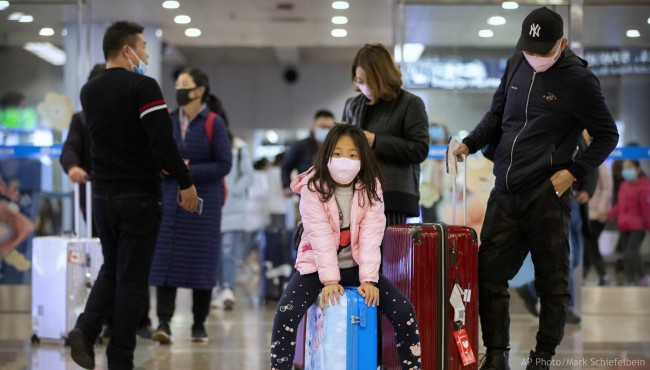 Travelers wear face masks as they stand in the arrivals area at Beijing Capital International Airport in Beijing, Thursday, Jan. 23, 2020. (AP Photo/Mark Schiefelbein)