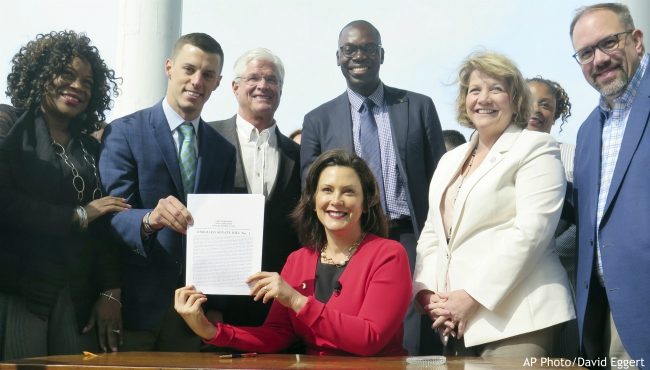 In this May 30, 2019, file photo, Michigan Gov. Gretchen Whitmer, seated, displays the auto insurance legislation she signed at the Detroit Regional Chamber's Mackinac Policy Conference at the Grand Hotel on Mackinac Island, Mich. Michigan residents will see new laws taking effect in the next two years, ranging from car insurance and sports betting, to E-cigarettes and online taxes. (AP Photo/David Eggert, File)