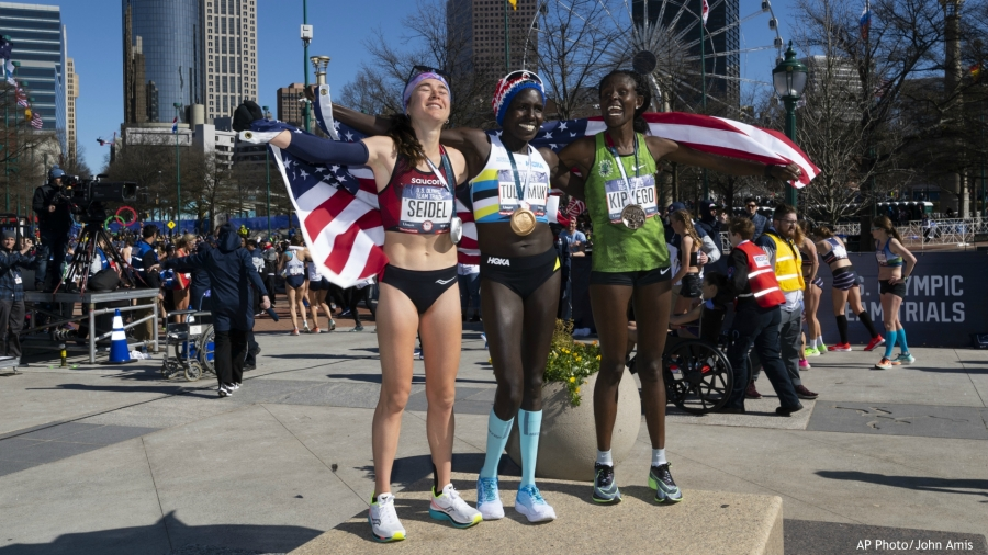First-place finisher Aliphine Tuliamuk, center, second-place finisher Molly Seidel, left, and third-place finisher Sally Kipyego, right, celebrate on the podium after running the women's U.S. Olympic marathon trials, Saturday, Feb. 29, 2020, in Atlanta. (AP Photo/John Amis)