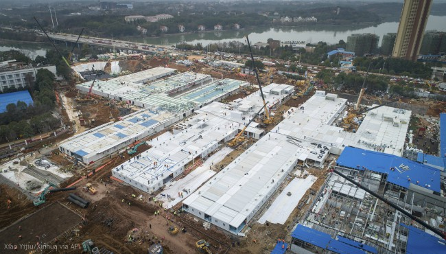 This Saturday, Feb. 1, 2020, photo released by China's Xinhua News Agency, shows construction workers at the site of the Huoshenshan temporary field hospital being built in Wuhan in central China's Hubei Province. (Xiao Yijiu/Xinhua via AP)