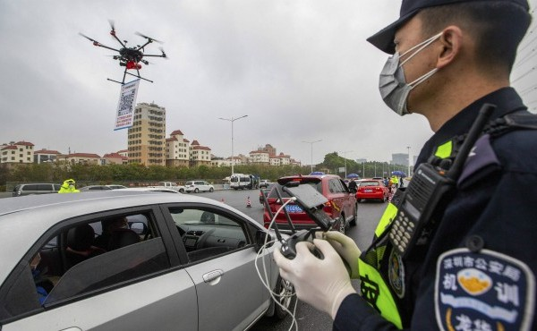 In this Tuesday, Feb. 11, 2020, photo released by China's Xinhua News Agency, a police officer operates a drone carrying a QR code placard near an expressway toll station in Shenzhen in southern China's Guangdong Province. (Lai Li/Xinhua via AP)