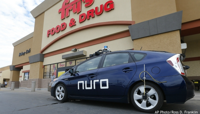 In this Aug. 16, 2018 file photo, a self-driving Nuro vehicle parks outside a Fry's supermarket in Scottsdale, Ariz. For the first time, the U.S. government's highway safety agency has approved a Nuro's request to deploy a self-driving vehicle that doesn't meet federal safety standards for human-driven cars and trucks. The National Highway Traffic Safety Administration granted temporary approval for the Silicon Valley robotics company to run a low-speed autonomous delivery vehicle without side and rear-view mirrors used by human drivers. (AP Photo/Ross D. Franklin, File)