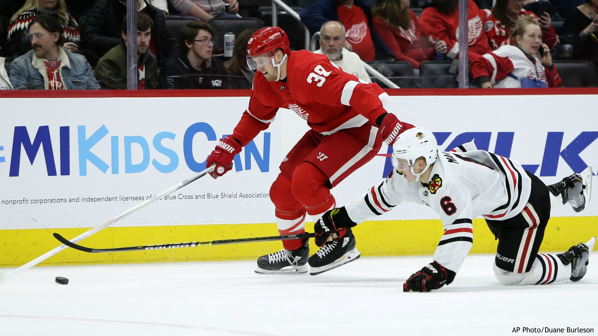 Chicago Blackhawks defenseman Olli Maatta (6) tries to steal the puck from Detroit Red Wings right wing Anthony Mantha (39) during the second period of an NHL hockey game Friday, March 6, 2020, in Detroit. (AP Photo/Duane Burleson)
