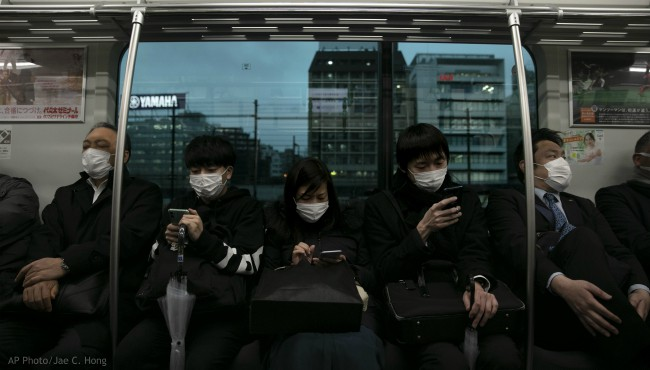 Commuters wearing masks sit on a train in Tokyo, Monday, March 2, 2020. (AP Photo/Jae C. Hong)