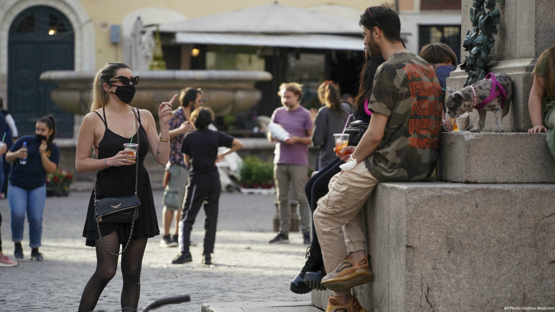 People enjoy a drink in Rome's fashionable Campo De' Fiori Square, as the city is slowly returning to life after the long shutdown due to the coronavirus outbreak, Friday, May 8, 2020. (AP Photo/Andrew Medichini)
