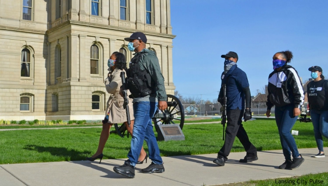 State Rep. Sarah Anthony, D-Lansing, escorted by armed activists on Wednesday, May 6, 2020. (Courtesy of the Lansing City Pulse)