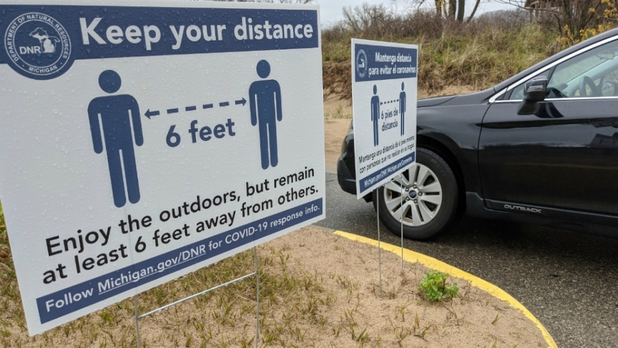 A sign reminding people to social distance at Holland State Park on May 14, 2020.