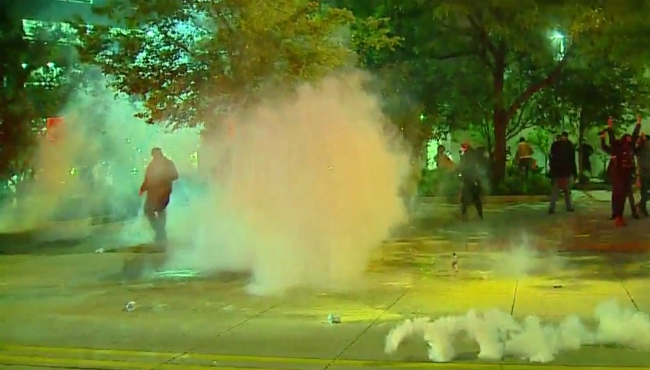 Police use gas to get a large, unruly crowd to break up after a protest over the death of George Floyd. (May 30, 2020)