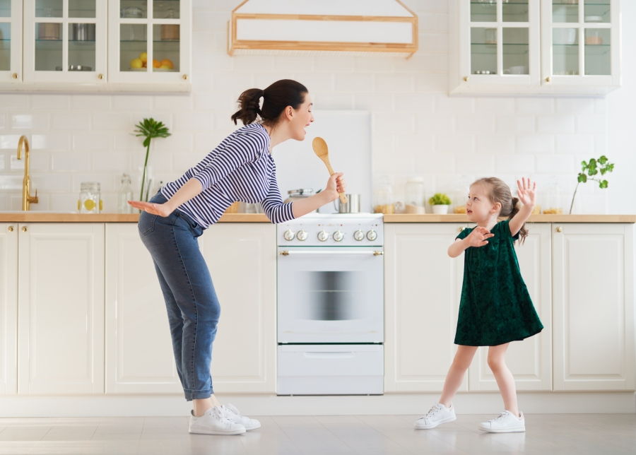 Child daughter and mom cooking and having fun in the kitchen at home. Family holiday and togetherness.
