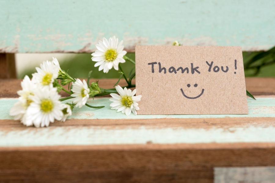 thank you note with smiley face and white flowers in background sitting on wooden table