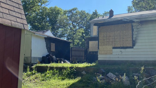 The space where police say the fire that killed Wanedia Scales and her three kids started. Officers report a burn pit was in place between the garage (left) and the home (right).