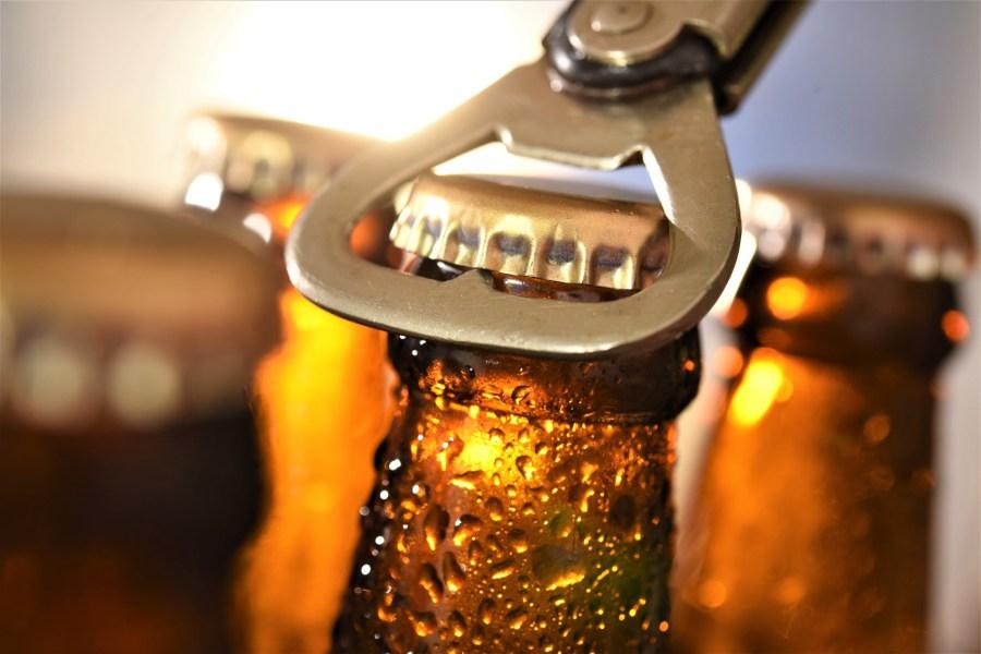Four empty bottles of beer being opened by metal bottle opener