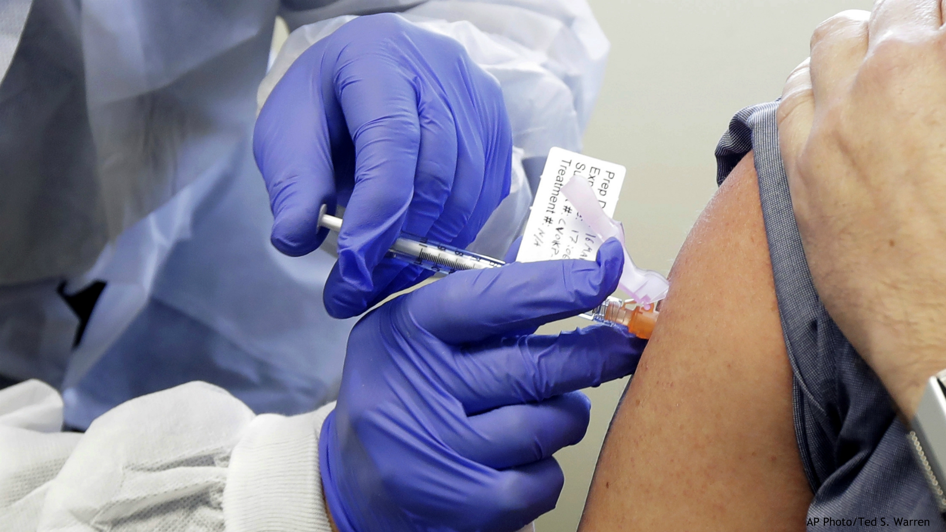 In this March 16, 2020, file photo, Neal Browning receives a shot in the first-stage safety study clinical trial of a potential vaccine for COVID-19, the disease caused by the new coronavirus, at the Kaiser Permanente Washington Health Research Institute in Seattle. (AP Photo/Ted S. Warren, File)