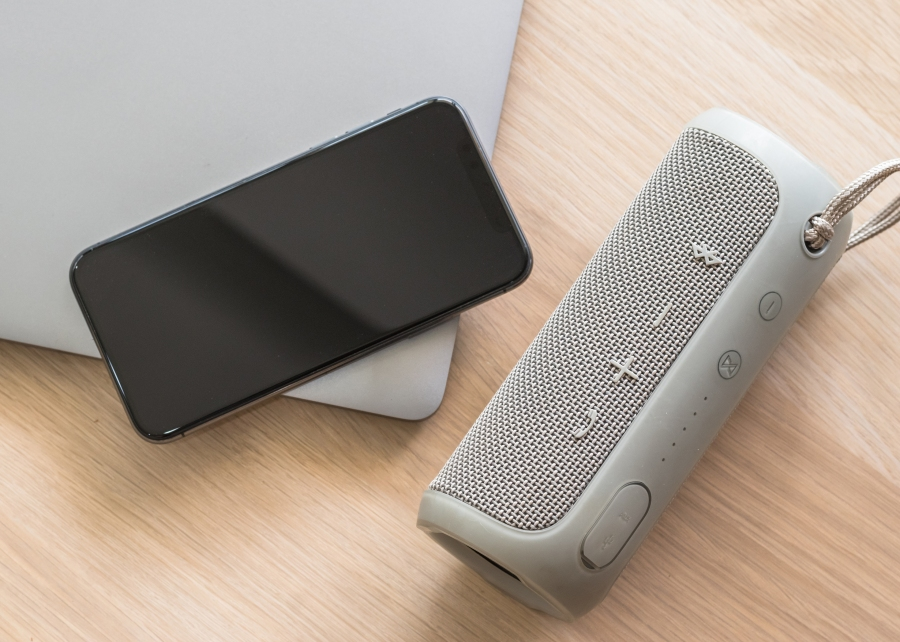 Smartphone, gray speaker, and gray laptop sitting on table