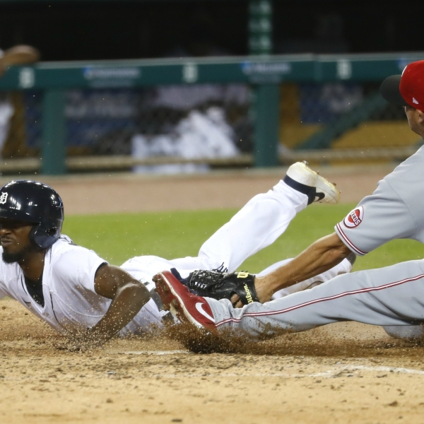 Detroit Tigers' Travis Demeritte beats the tag of Cincinnati Reds relief pitcher Nate Jones (57) to score at home plate on a wild pitch in the seventh inning of a baseball game in Detroit, Friday, July 31, 2020. (AP Photo/Paul Sancya)