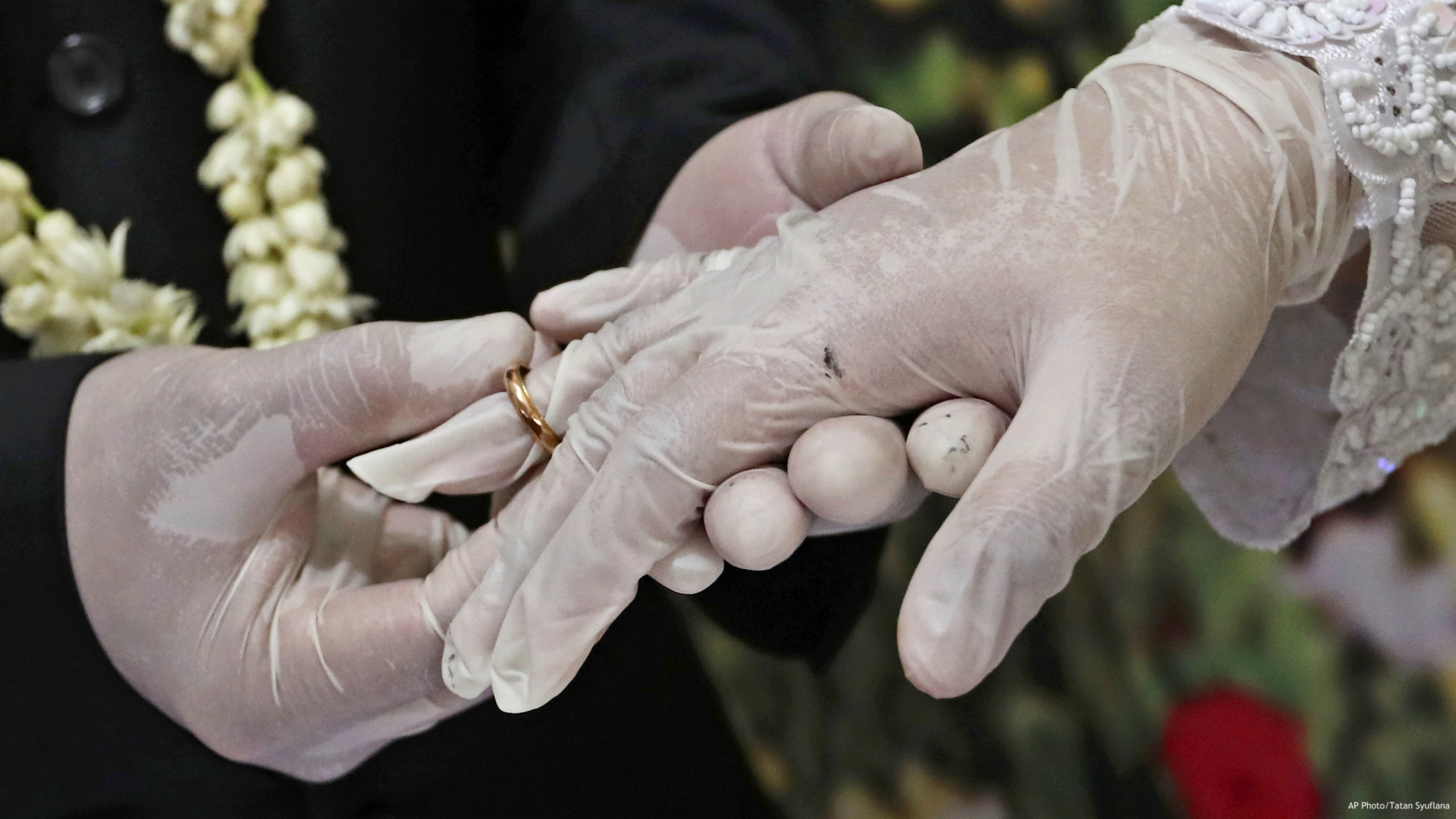 Wearing latex gloves to prevent the spread of the coronavirus, a bride and groom exchange rings during their wedding ceremony at the local Religious Affairs Office in Pamulang, on the outskirts of Jakarta, Indonesia, on June 19, 2020. Now that weddings have slowly cranked up under a patchwork of ever-shifting restrictions, horror stories from vendors are rolling in. Many are desperate to work after the coronavirus put an abrupt end to their incomes and feel compelled to put on their masks, grab their cameras and hope for the best. (AP Photo/Tatan Syuflana, File)