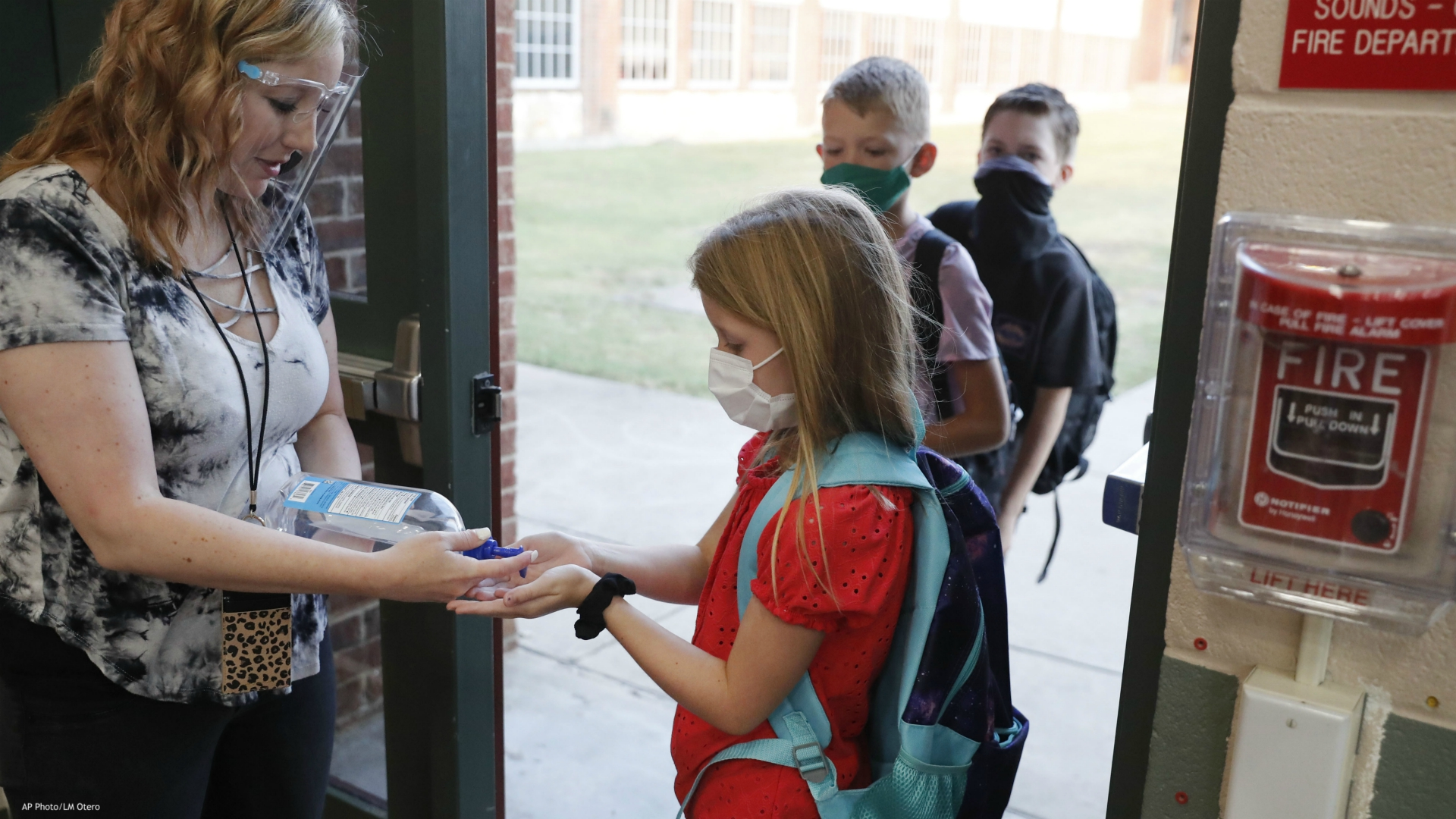 In this Aug. 5, 2020, file photo, wearing masks to prevent the spread of COVID19, elementary school students use hand sanitizer before entering school for classes in Godley, Texas. As schools reopen around the country, their ability to quickly identify and contain coronavirus outbreaks before they get out of hand is about to be put to the test. (AP Photo/LM Otero, File)