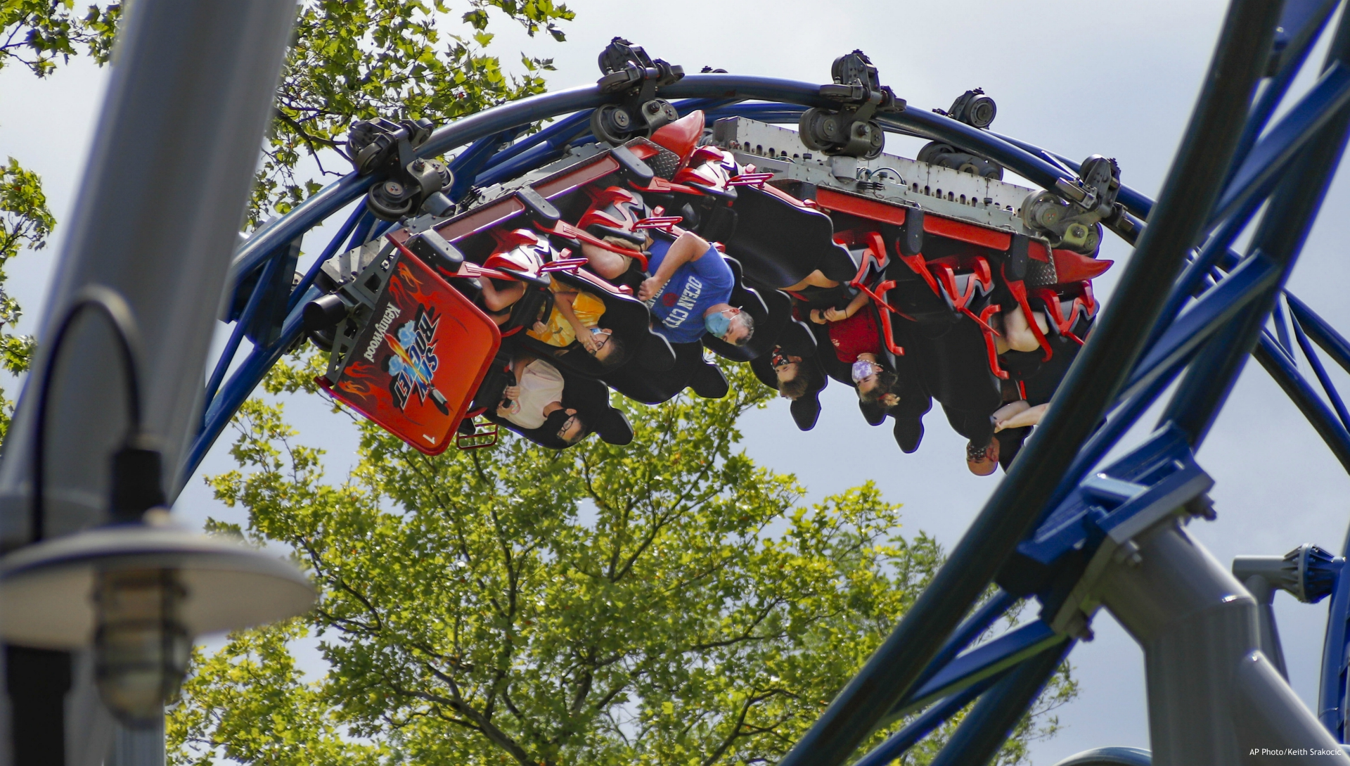 """In this photo made on Saturday, Aug. 29, 2020, riders of the """"Phantoms Revenge"""" roller coaster are inverted as they go through a loop during the ride at Kennywood Park in West Mifflin, Pa. Visitors have been slow to return to U.S. theme parks that saw their seasons interrupted by the coronavirus crisis, causing some parks to reduce their operating days, slash ticket prices and close early for the year. (AP Photo/Keith Srakocic)"""