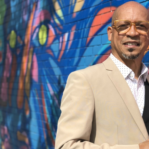 A photo of Caribbean artist Erick Picardo in front his mural in Grand Rapids.