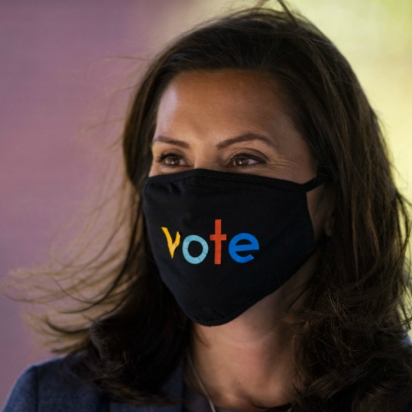 "Michigan Gov. Gretchen Whitmer wears a mask with the word ""vote"" displayed on the front during a roundtable discussion on healthcare, Wednesday Oct. 7, 2020, in Kalamazoo, Mich. The arrest of a group of anti-government vigilantes in a kidnapping plot against Michigan Gov. Gretchen Whitmer presents a new twist in the 2020 political fight for the battleground state. (Nicole Hester/Ann Arbor News via AP)/"