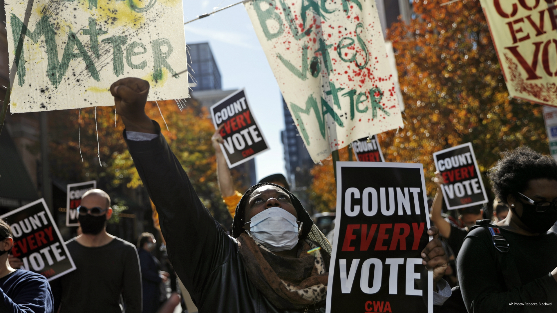 In this Nov. 5, 2020, file photo, Zhanon Morales, 30, of Philadelphia, raises her fist as demonstrators call for all votes be counted during a rally outside the Pennsylvania Convention Center in Philadelphia, as vote counting in the general election continues. A tough road lies ahead for Biden who will need to chart a path forward to unite a bitterly divided nation and address America's fraught history of racism that manifested this year through the convergence of three national crises. (AP Photo/Rebecca Blackwell, File)