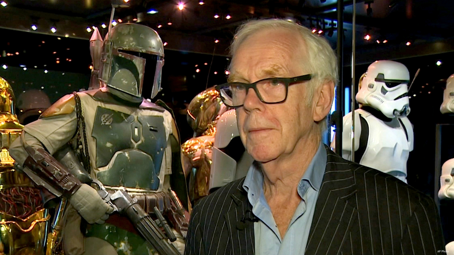 """Jeremy Bulloch speaks in front of the costume he wore while playing Boba Fett in """"Star Wars: Episode V – The Empire Strikes Back"""" and """"Star Wars: Episode VI – Return of the Jedi"""" at the Star Wars Identities exhibition in London on July 26, 2017. Bulloch, the English actor who played Boba Fett in the original """"Star Wars"""" trilogy, has died. His agents said in a statement that he died in a London hospital Thursday, Dec. 17, 2020, after years of suffering from Parkinson's disease. He was 75. (AP Photo)"""