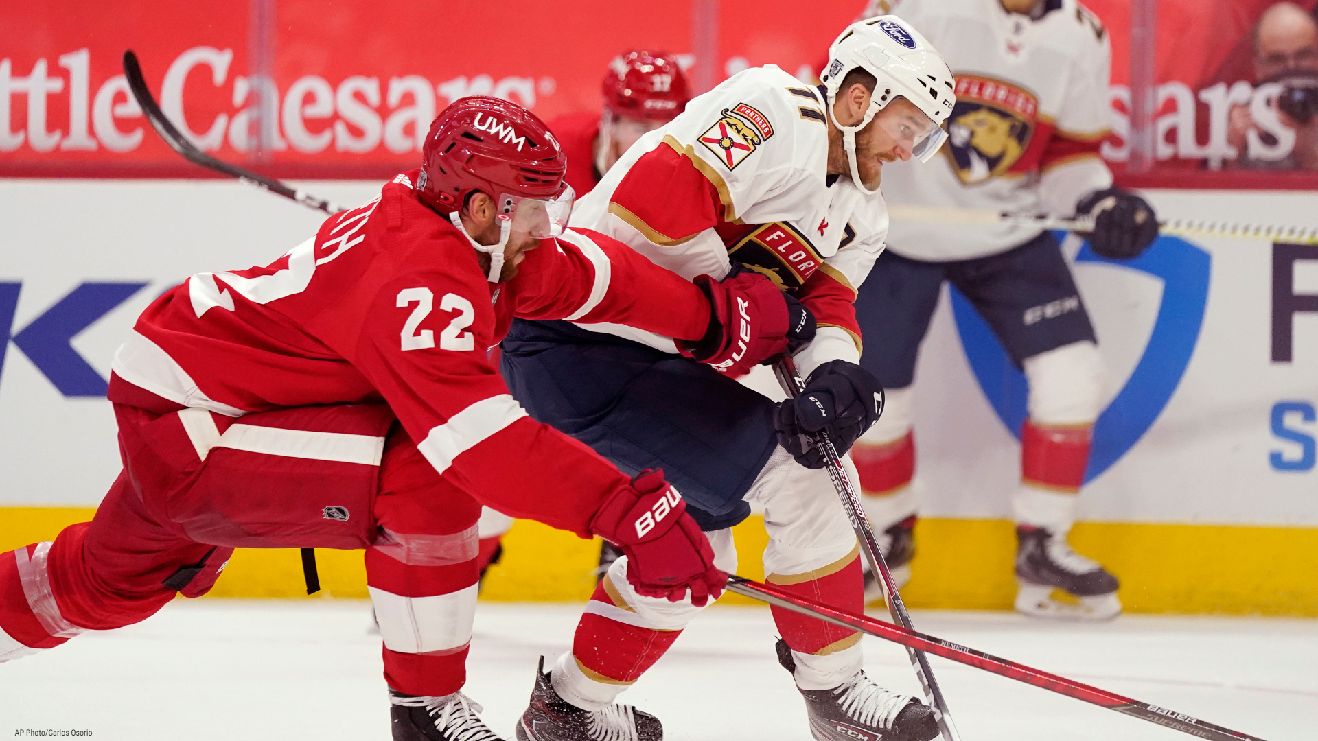 Detroit Red Wings defenseman Patrik Nemeth (22) and Florida Panthers left wing Jonathan Huberdeau (11) chase the puck during the first period of an NHL hockey game, Saturday, Jan. 30, 2021, in Detroit. (AP Photo/Carlos Osorio)