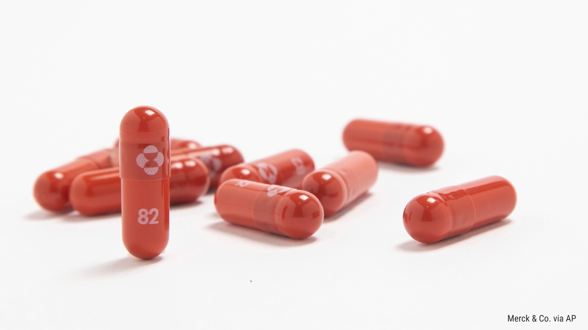 about nine red capsules with white labeling rest on a white background
